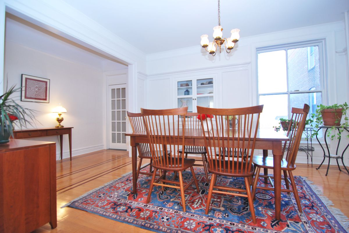 A dining area with a wood dining table, a chandelier, and a colorful rug.