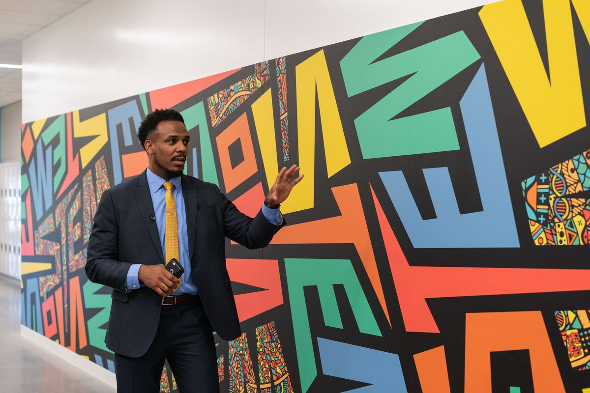 Conrad Timbers-Ausar, Englewood STEM High School's principal, shows off a mural at the South Side school