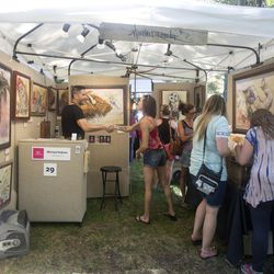Michael Rohner, left, greets and introduces himself to patrons in his booth on the first day of the Utah Arts Festival in Salt Lake City on Thursday, June 22, 2017.