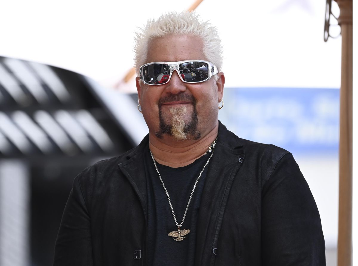 Guy Fieri wearing sunglasses, a black leather jacket, and a gold necklace.