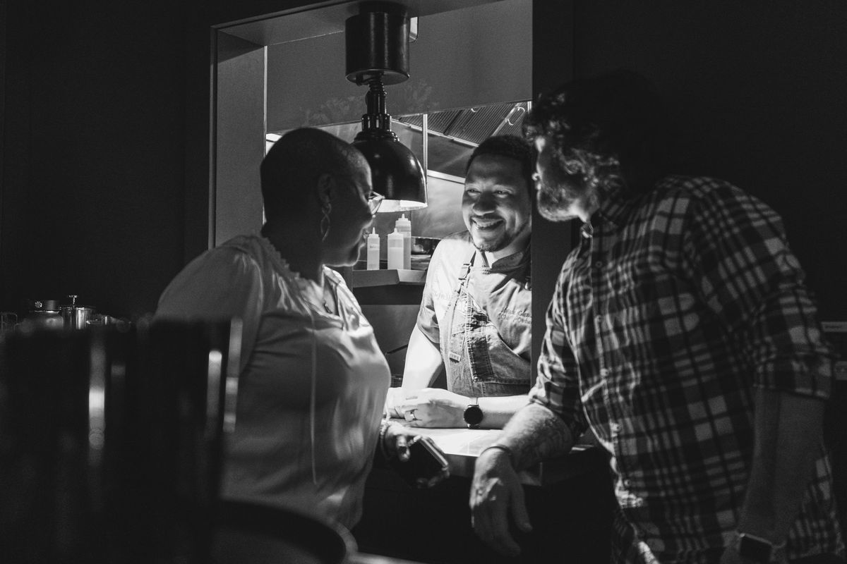 Nelson German (center) smiling as he talks to another chef at his bar-restaurant Sobre Mesa
