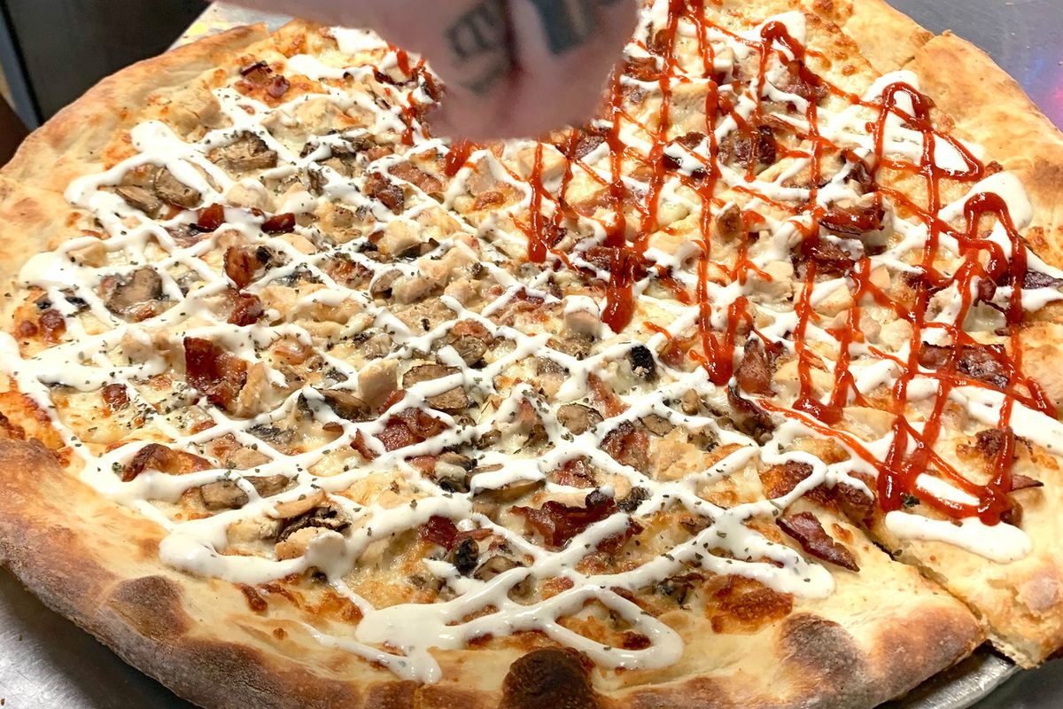 A pizza with sausage and sauce