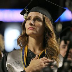 Salt Lake Community College graduate Joelle Merriman stands during the national anthem during the school's commencement at the Maverick Center in West Valley City Friday, May 6, 2016.
