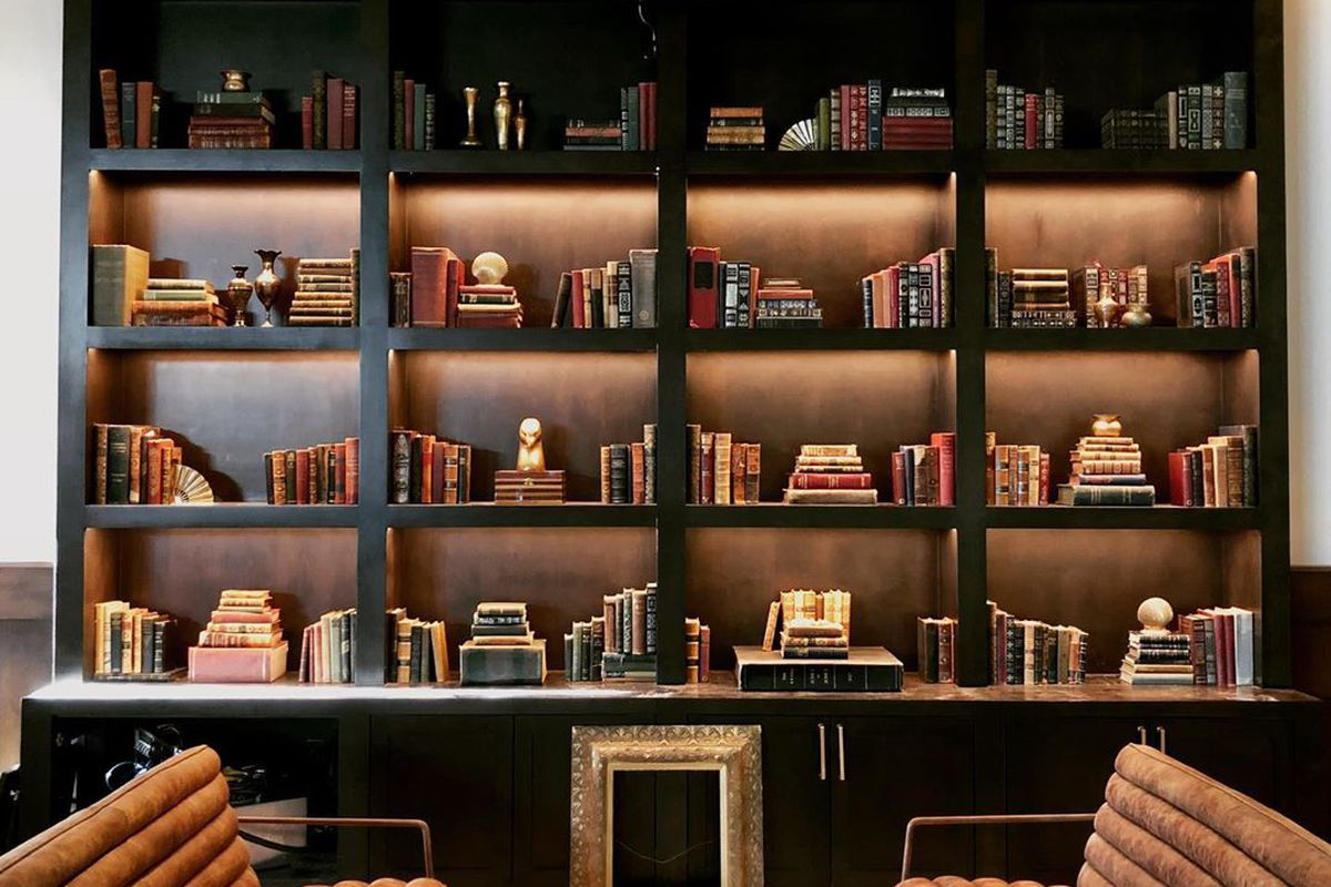 A library wall of books and shelves at an upcoming Los Angeles supper club.
