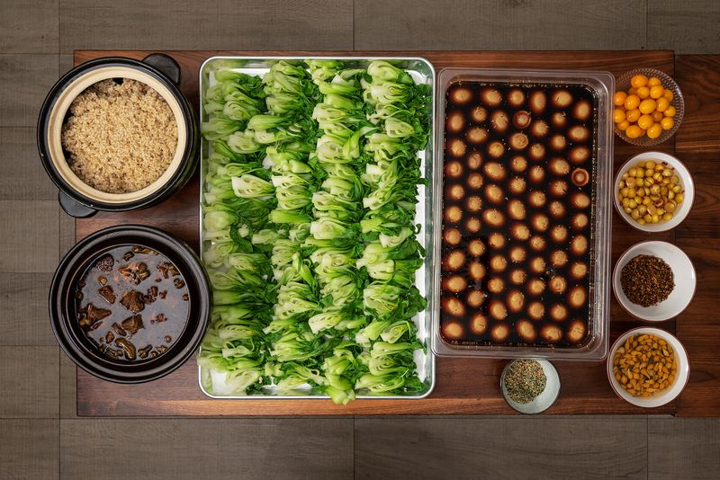 Sheet pans filled with bok choy and cooked eggs sit alongside bowls of rice, stewed meats, and other accompaniments on a tabletop.
