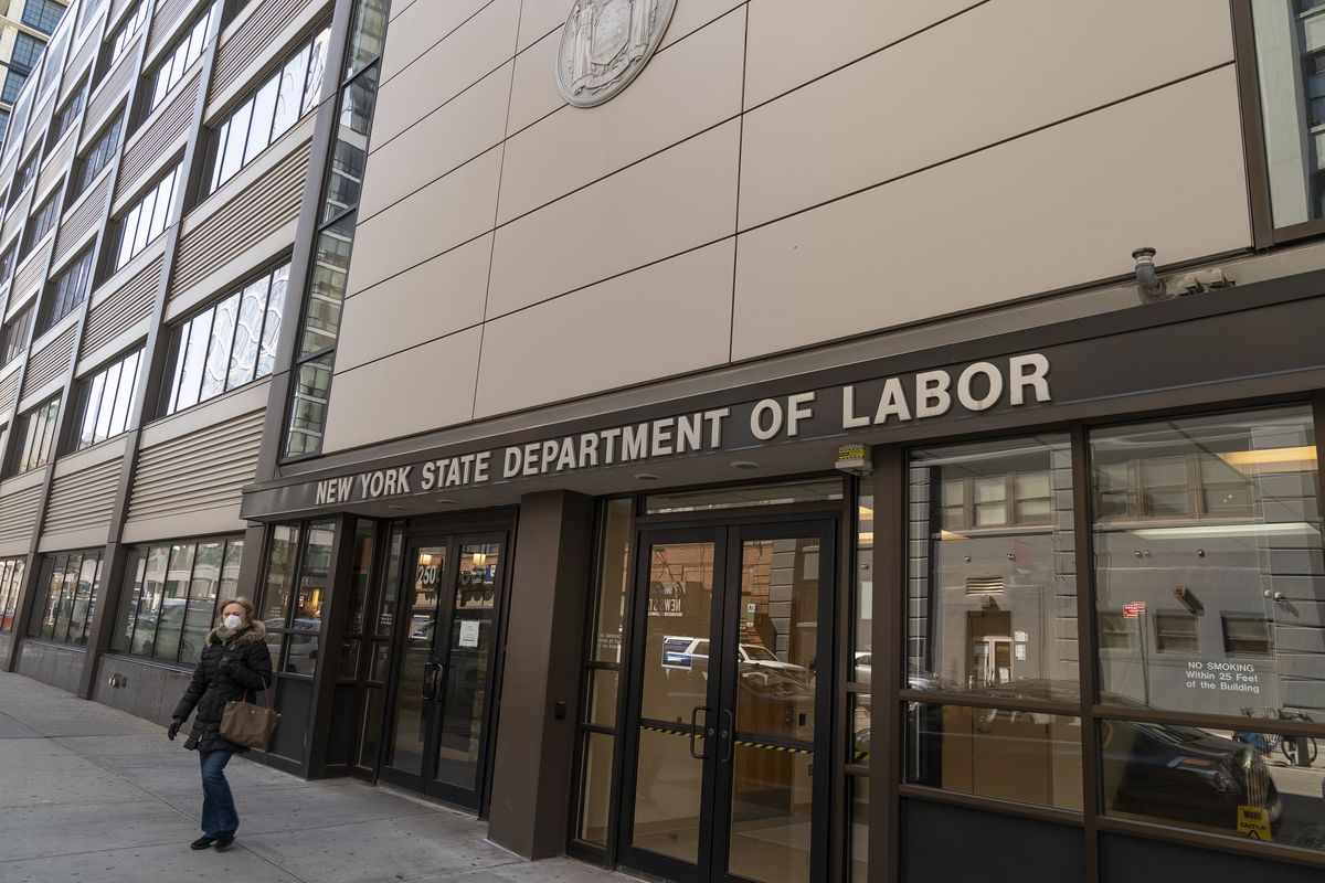 The exterior of an office building with brown and beige colors and the sign says new york state department of labor