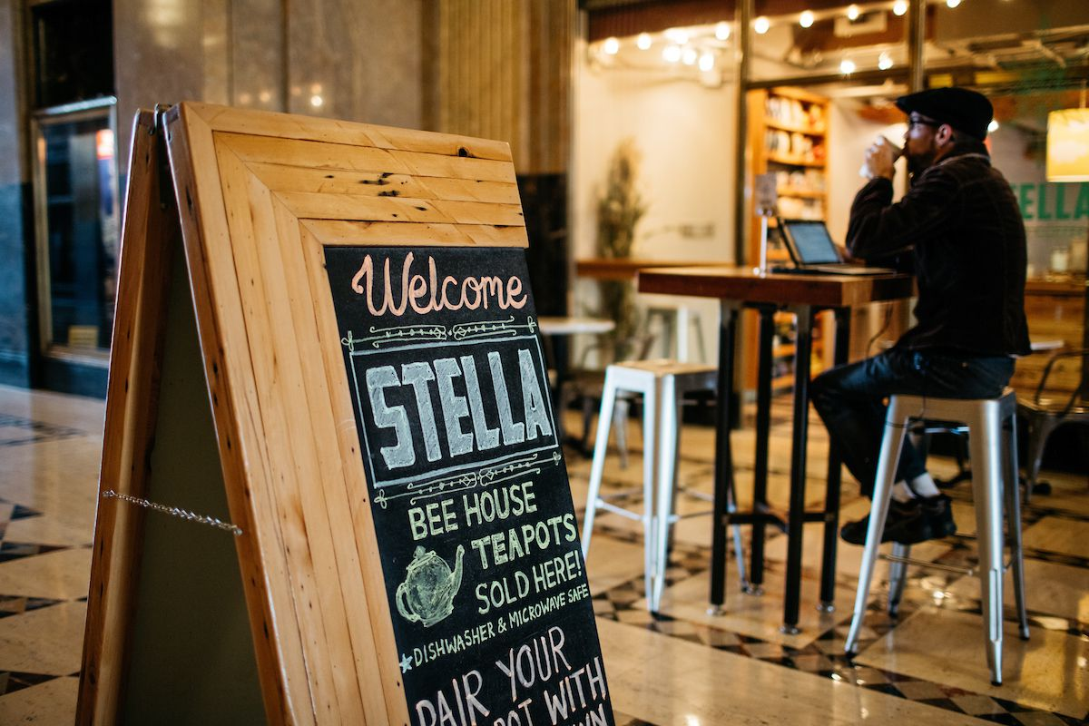 """A sandwich board says """"Welcome to Stella"""" as a man works on a laptop at a table outside the coffee shop."""