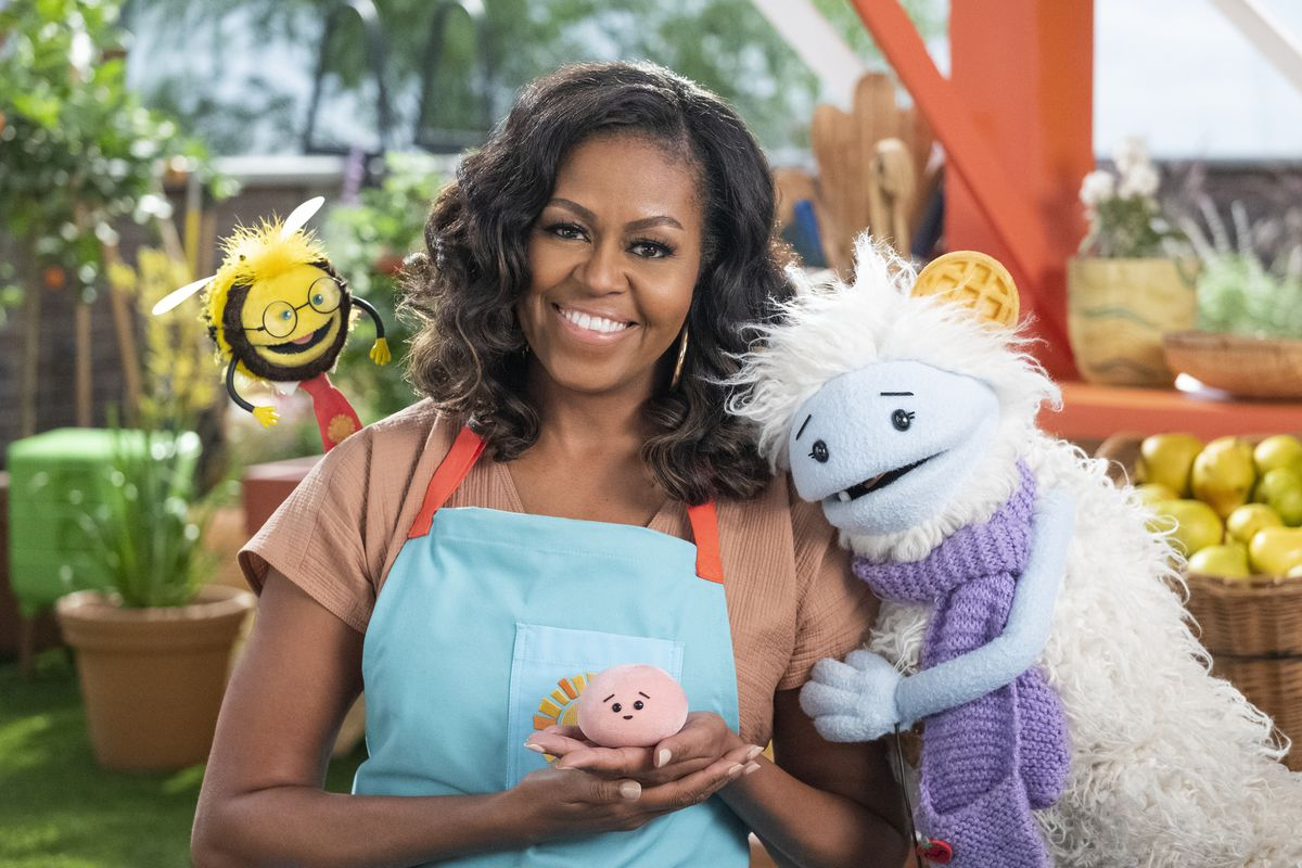 """Former first lady Michelle Obama poses with Busy, a bee puppet (from left) Mochi, a pink round puppet, and Waffles, a furry puppet with waffle ears on the set of the children's series """"Waffles + Mochi."""""""