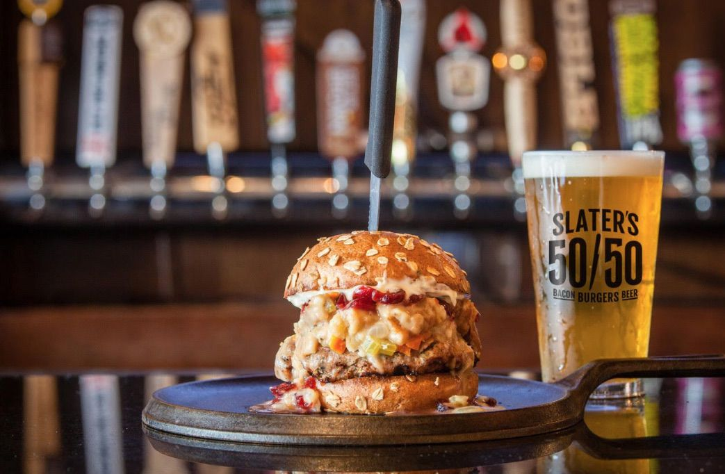A turkey burger next to a pint of beer with beer taps behind both