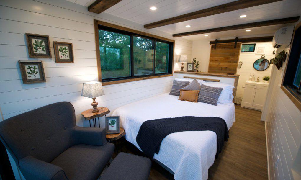 Queen bed in wood paneled bedroom