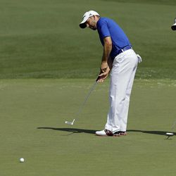 Sergio Garcia, left, of Spain, and Luke Donald, of England, putt on the second green during a practice round for the Masters golf tournament Wednesday, April 4, 2012, in Augusta, Ga.