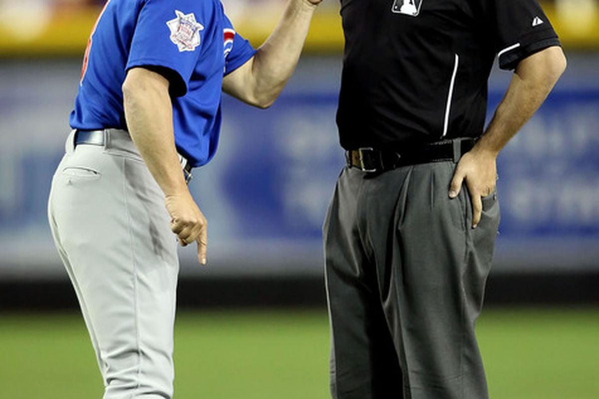 Write your own caption: what is Mike Quade telling umpire Dan Bellino? (And why does he have sunglasses on his cap during a night game?) (Photo by Christian Petersen/Getty Images)