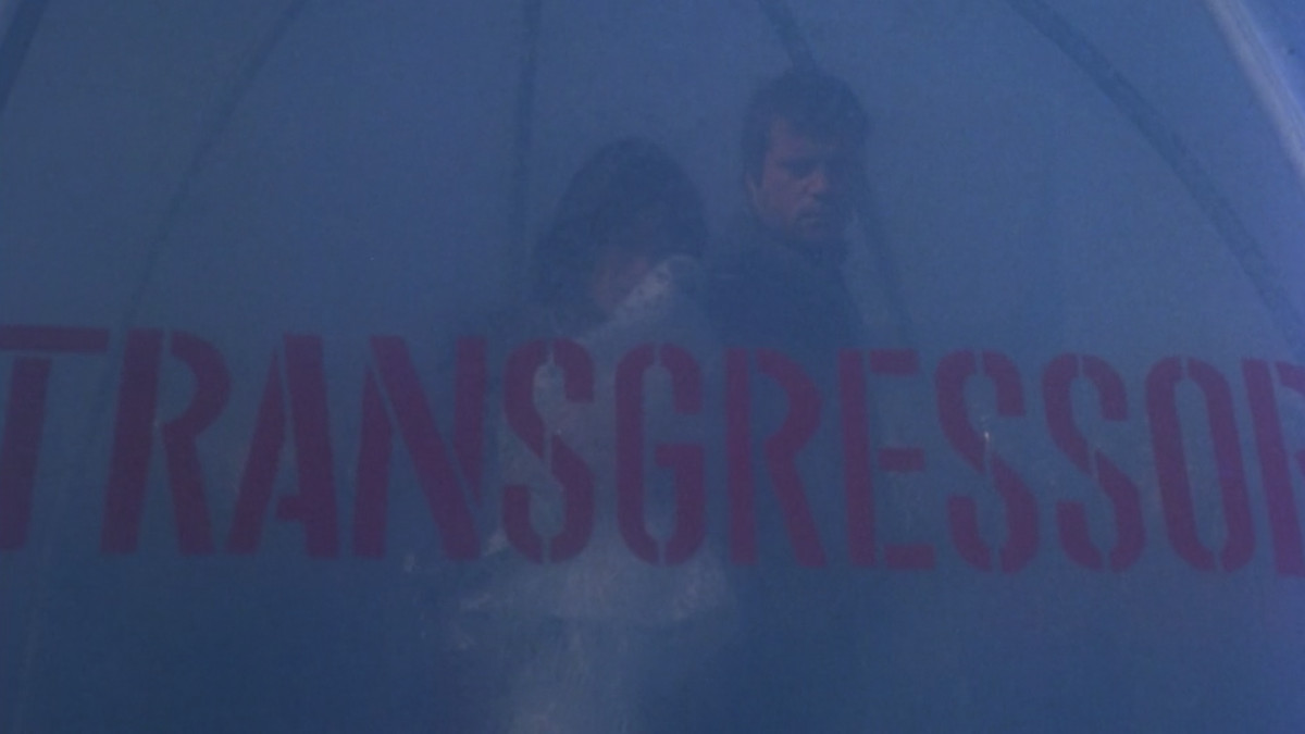 The stars of ZPG are dimly visible behind a huge stenciled sign that reads TRANSGRESSION in red