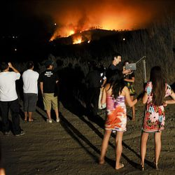 Residents look on as a firefighting helicopter drops water on a fast moving brush fire that broke out in Rancho Palos Verdes, Calif., shortly after 8:00 p.m., Thursday.