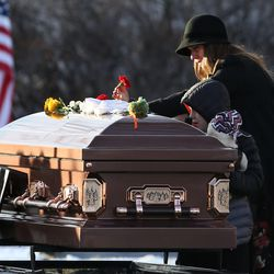 Janica Ellsworth, wife of Utah Highway Patrol trooper Eric Ellsworth, and two of their three sons place flowers on his casket at the Brigham City Cemetery on Wednesday, Nov. 30, 2016. Trooper Ellsworth died Tuesday, Nov. 22, four days after he was hit by a 16-year-old driver while attempting to slow traffic in Garland because of a problem with a power line.