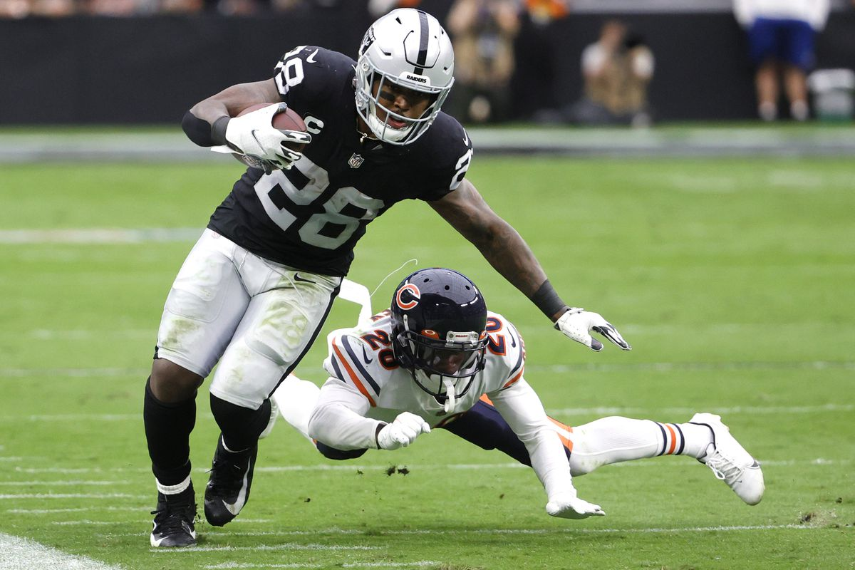 Josh Jacobs #28 of the Las Vegas Raiders runs with the ball as Duke Shelley #20 of the Chicago Bears defends during the first half at Allegiant Stadium on October 10, 2021 in Las Vegas, Nevada.