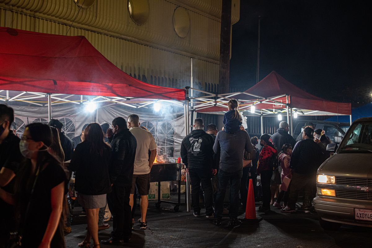 Families crowd around a smoky stand at a night market.