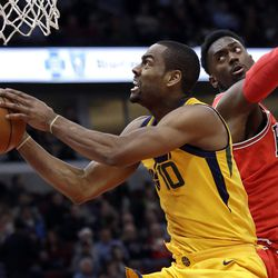 Utah Jazz guard Alec Burks, left, drives to the basket past Chicago Bulls forward Bobby Portis during the second half of an NBA basketball game Wednesday, Dec. 13, 2017, in Chicago. The Bulls won 103-100. (AP Photo/Nam Y. Huh)