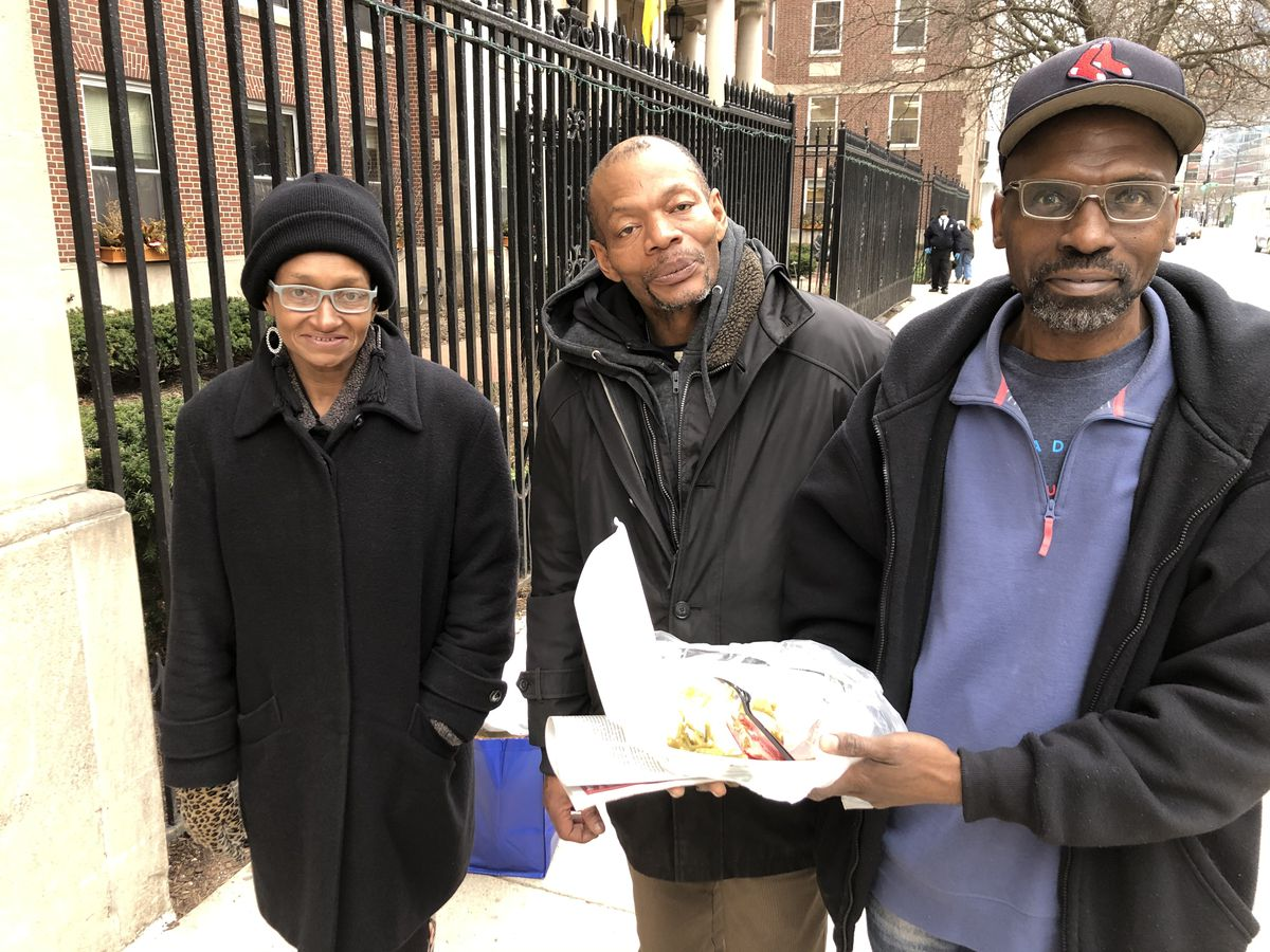 Carolyn Suttle, Aaron Curry and Kurt Jones pause to talk after picking up free meals from Catholic Charities.
