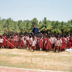 Utah resident and former NBA player Shawn Bradley stands among a group of children at the Rising Star Outreach campus in Thottanaval, India.