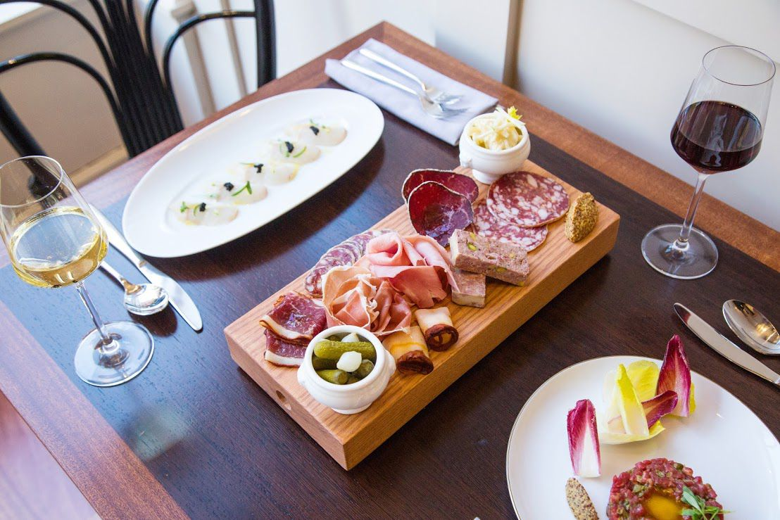 Charcuterie, cheese, and wine on a brightly lit table.