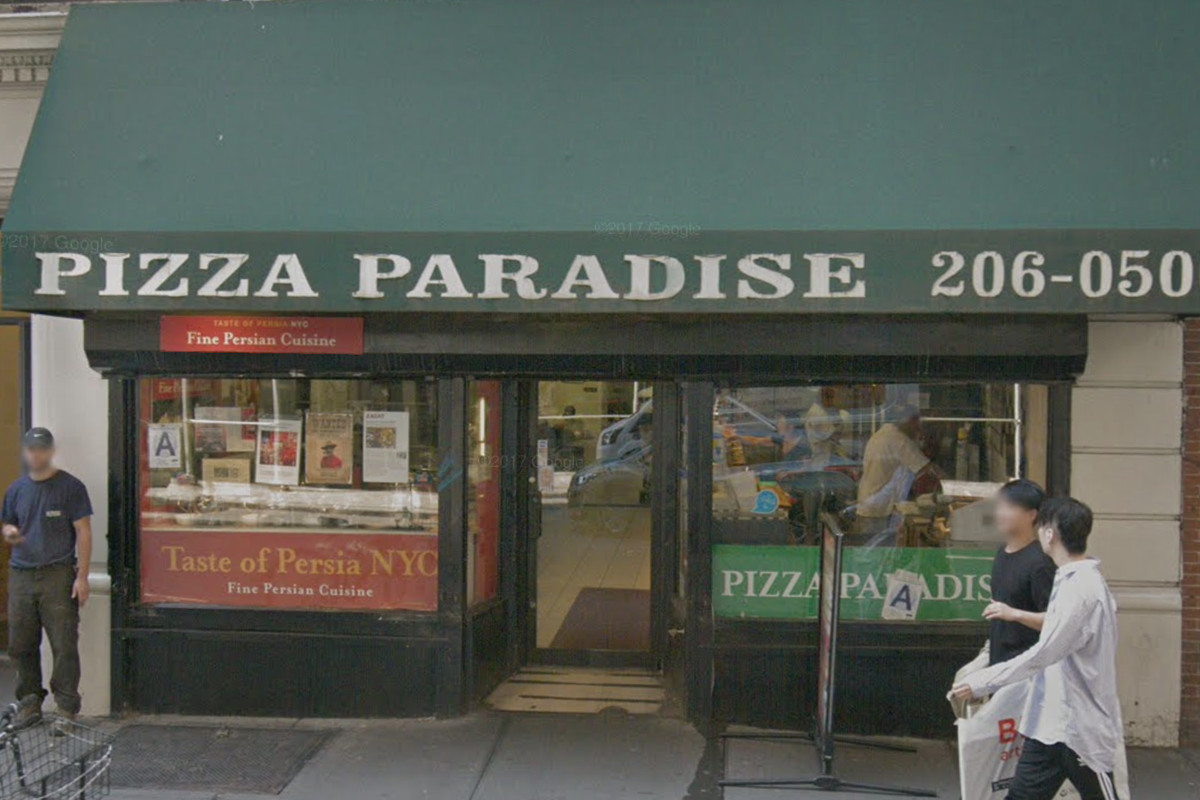 The exterior of the Persian restaurant Taste of Persia tucked into a pizzeria with a green awning. Taste of Persia has red signage out front.