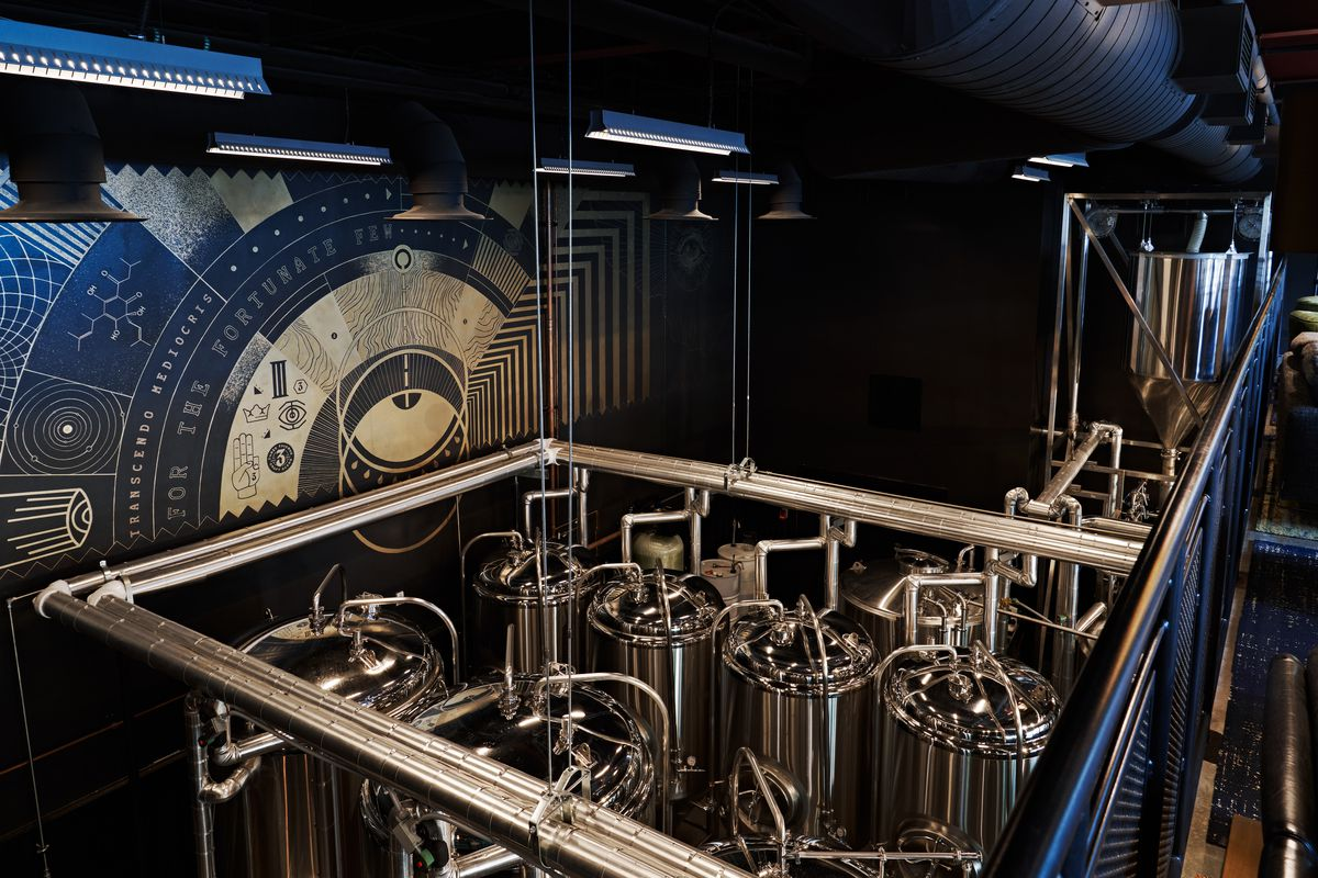 Overlooking the eight shiny metal brew tanks from the upstairs seating area in front of a blue astrological chart