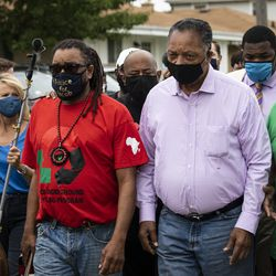Jacob Blake's uncle, Justin Blake, walks with Rev. Jesse Jackson during a community event hosted by the Blake family on the block where Jacob Blake was shot in the back by a Kenosha police officer, Tuesday morning, Sept. 1, 2020. President Donald Trump is scheduled to visit Kenosha Tuesday afternoon to meet with local officials and survey areas affected by the unrest in the wake of the shooting.