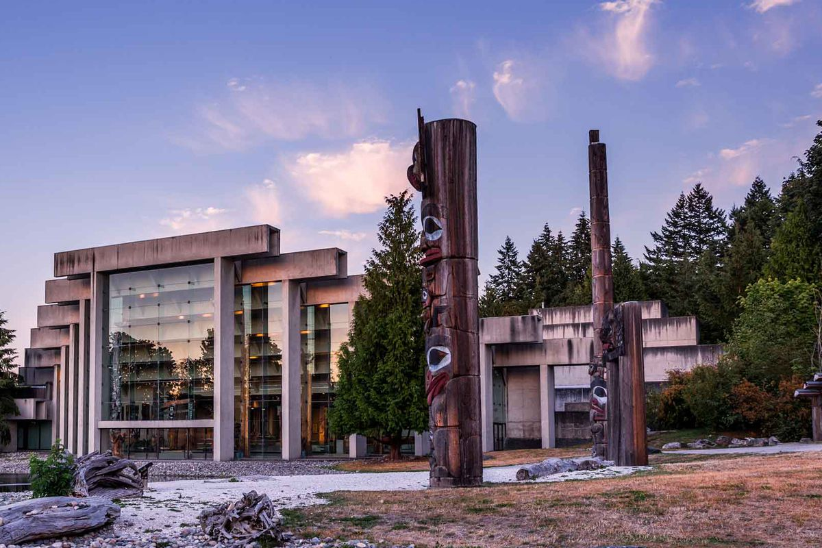 Modern concrete building with wall of glass and totem-like sculptures on the grounds surrounding it.