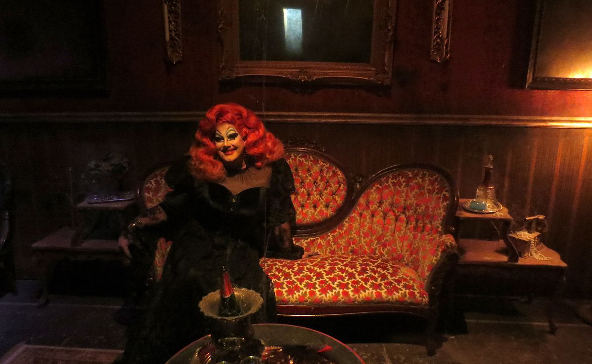 A woman (actually a man in drag) with heavy makeup, a bright orange wig, and a long black dress, posing on a red chaise lounge (actually a set).