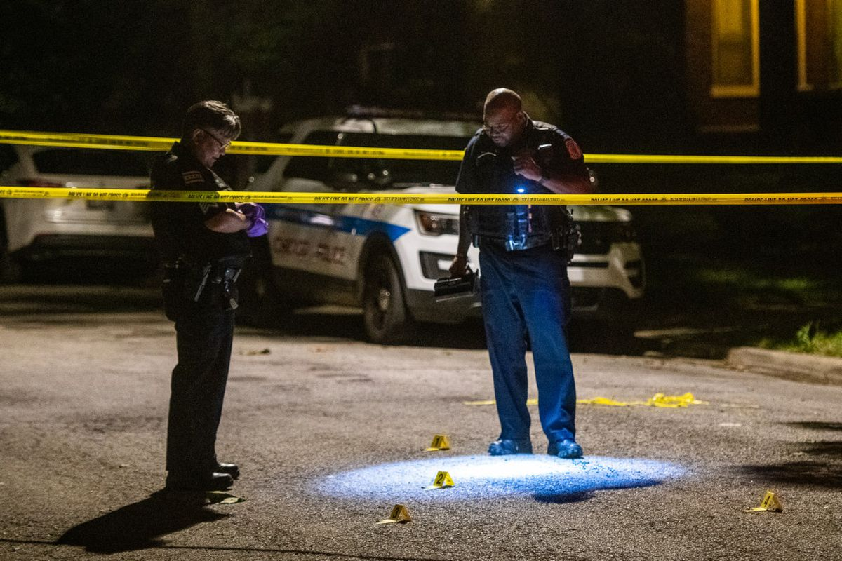 Police investigate the scene where two males were shot in Roseland on the South Side.