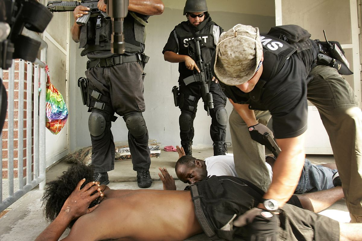 Police raid a New Orleans housing project in the aftermath of Hurricane Katrina.