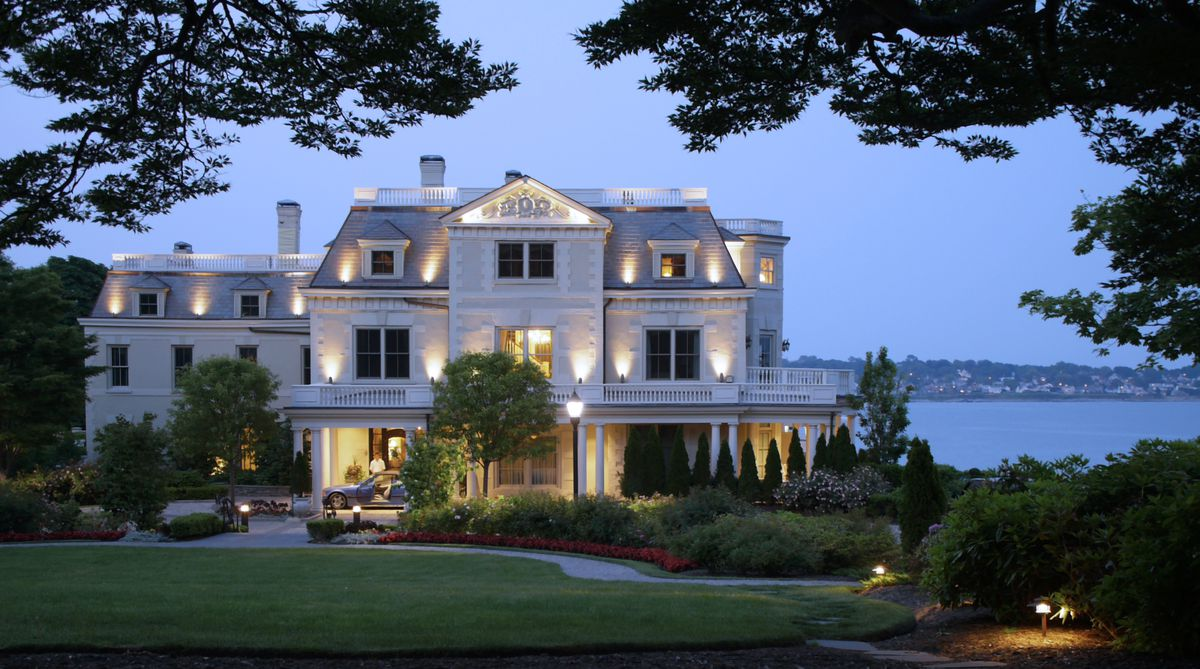 The exterior of the Chanler at Cliff Walk in Rhode Island. The facade is white. There are gardens in front. In the background is a body of water.