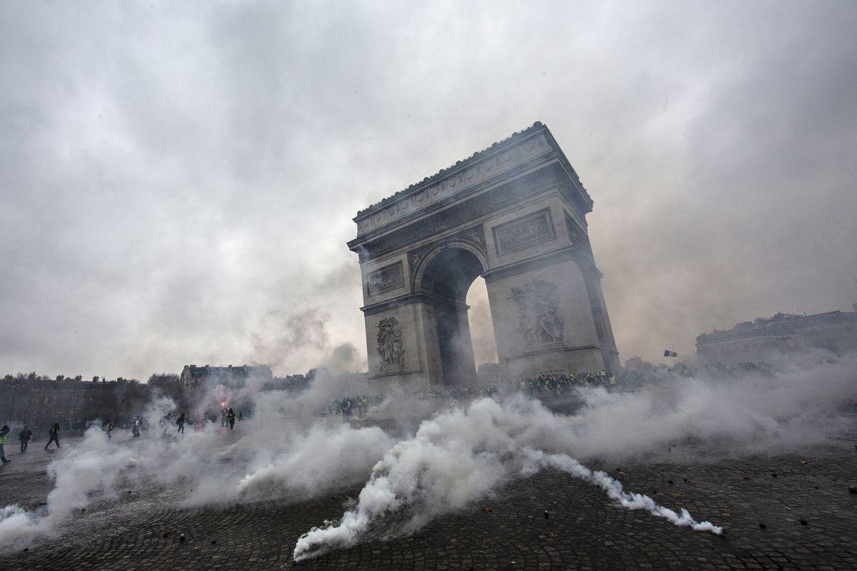 tear gas surrounds riot police as they clash with protesters during a yellow vest demonstration near the arc de triomphe on december 1st in paris
