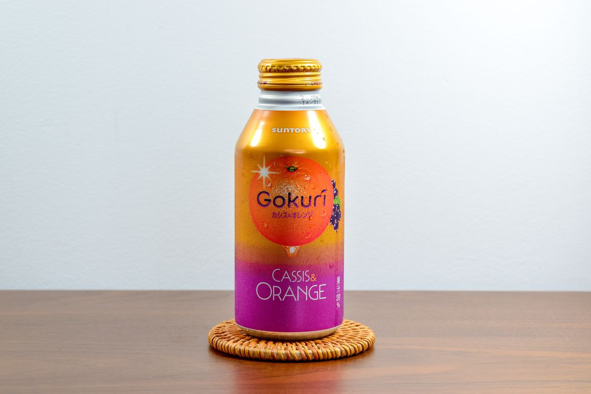 A bottle of Gokuri cassis and orange drink atop a coaster on a wooden tabletop.