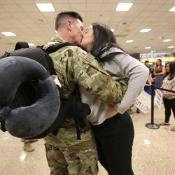 Sgt. James Dansie kisses his wife Amelia Dansie at the Salt Lake International Airport in Salt Lake City on Tuesday, Aug. 27, 2019, as he and other members of the Utah National Guard's 4th Infantry Division Main Command Post Operational Detachment return home after serving in Afghanistan for 10 months in support of Operation Freedom's Sentinel.