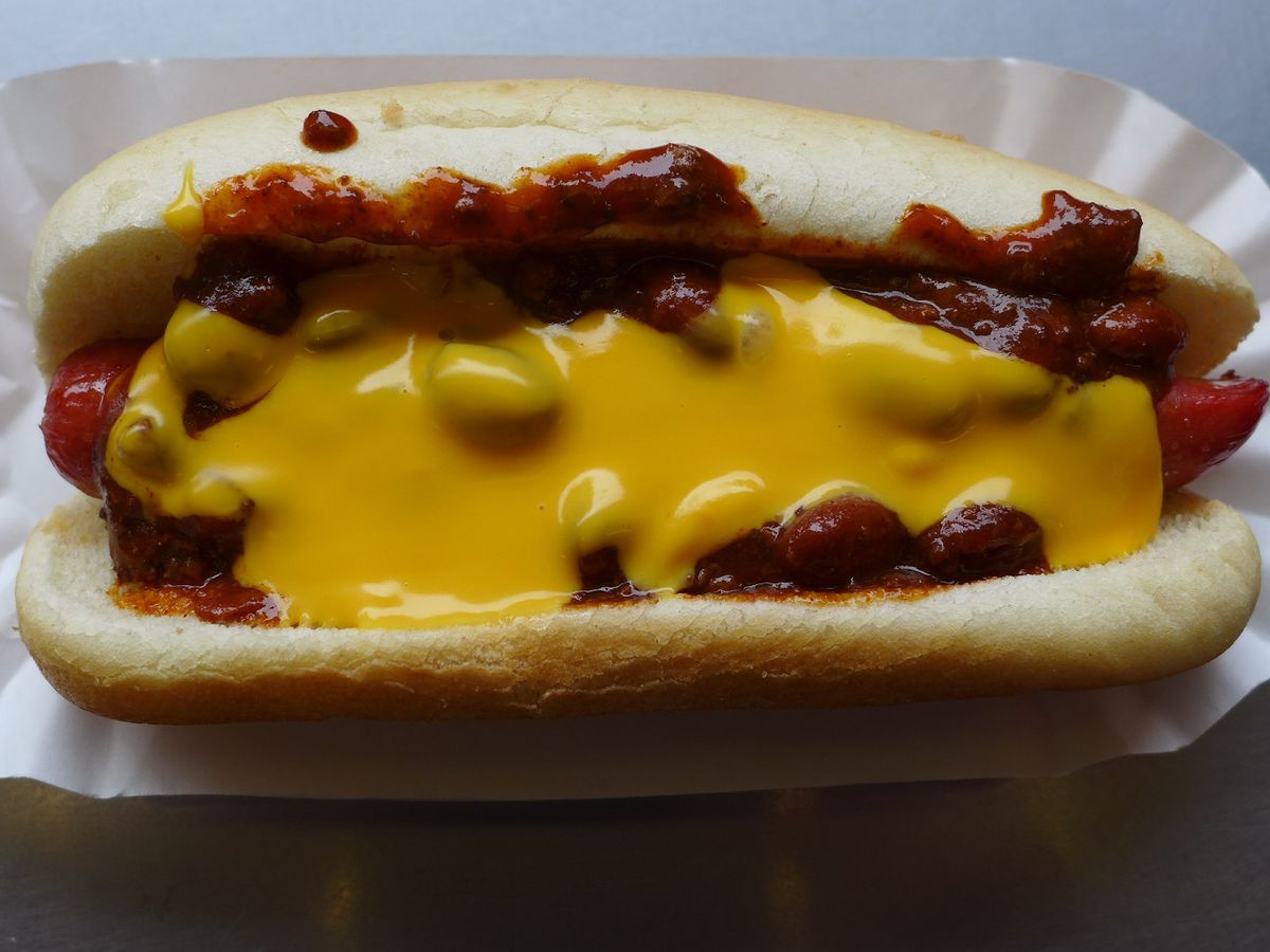 A hot dog in a bun smothered in yellow and with beans sticking out.