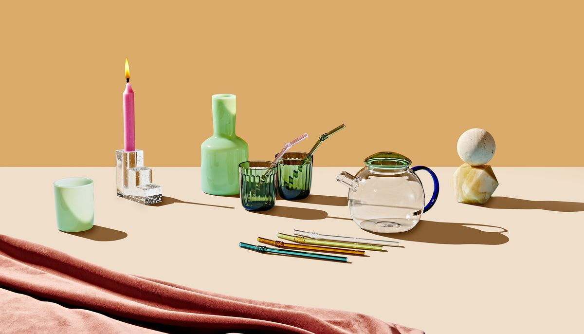 A group of products which are all featured in the 2019 Holiday Gift Guide for Curbed. There is a teapot, tumblers, multicolored glass straws, a carafe, and a candleholder. The products are sitting on a flat surface and there is an orange backdrop.