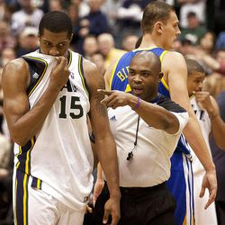 Jazz forward Derrick Favors (15) is led away from a brawl by a referee during the first half of the NBA basketball game between the Utah Jazz and the Golden State Warriors at Energy Solutions Arena, Wednesday, Dec. 26, 2012.