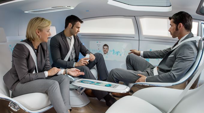 Passengers in Mercedes Benz's concept F 015 play with their gadgets.