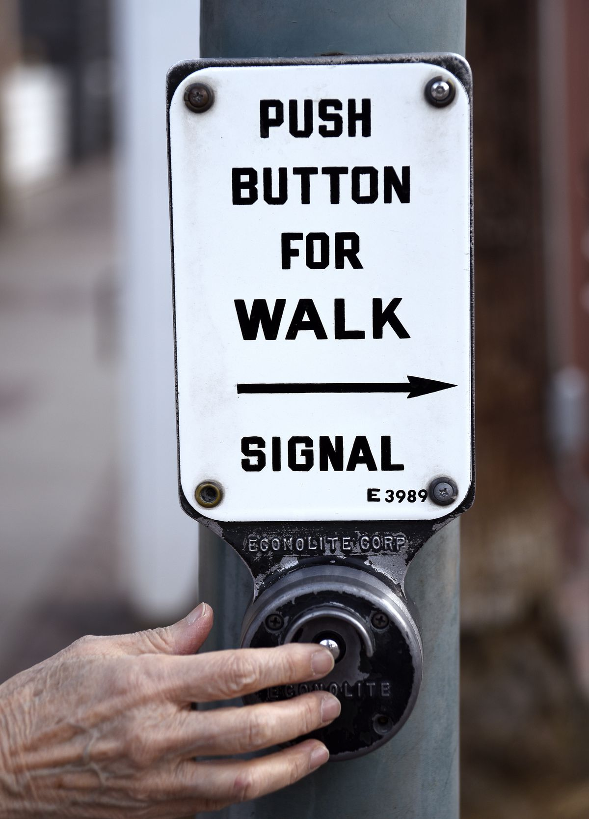 """A hand pressing a small metal button on the side of a pole, labeled """"push button for walk signal."""""""