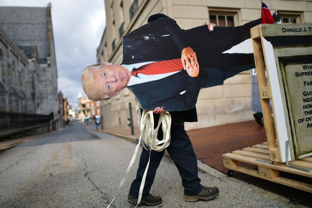 Two legs in black pants stick out from a giant cutout of Trump in a dark suit, white shirt, and red tie, his blonde hair neatly arranged on his head. The person carrying the cutout walks to the right, seemingly about to enter an alley. Old stone buildings loom behind them.