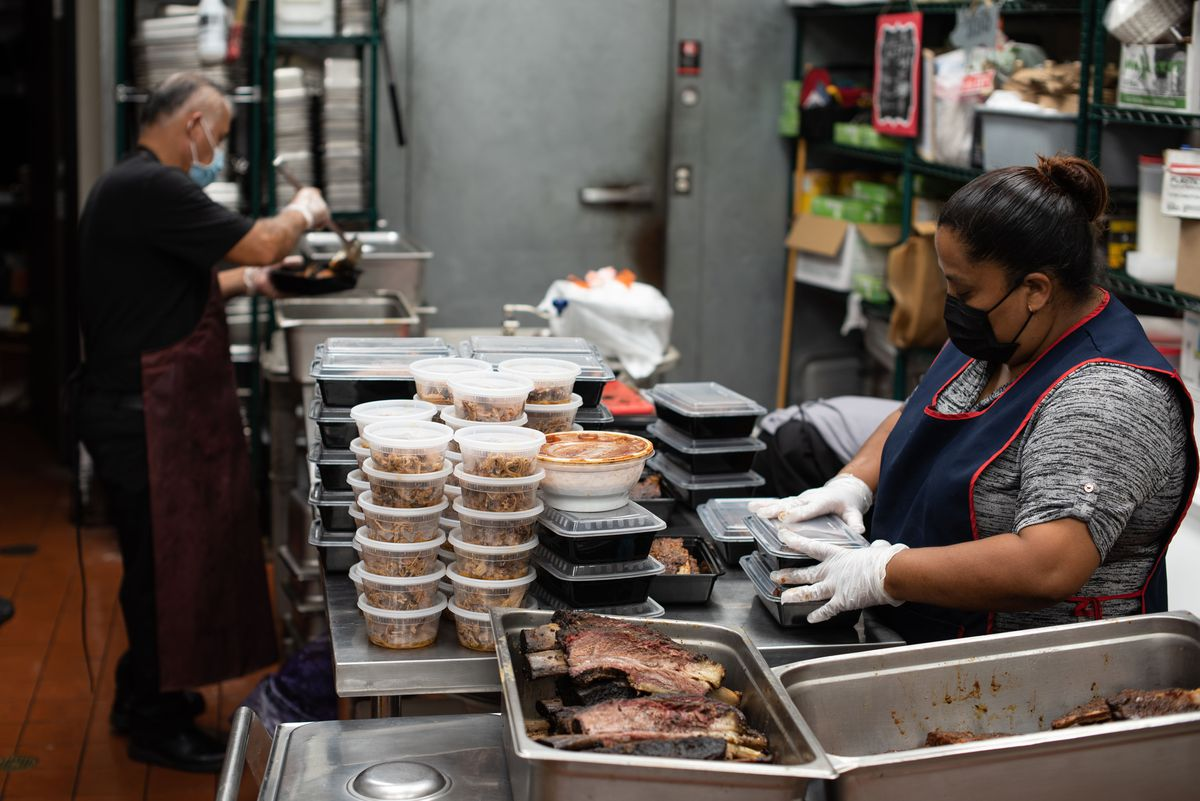A worker packages orders of barbecue inside a restaurant.