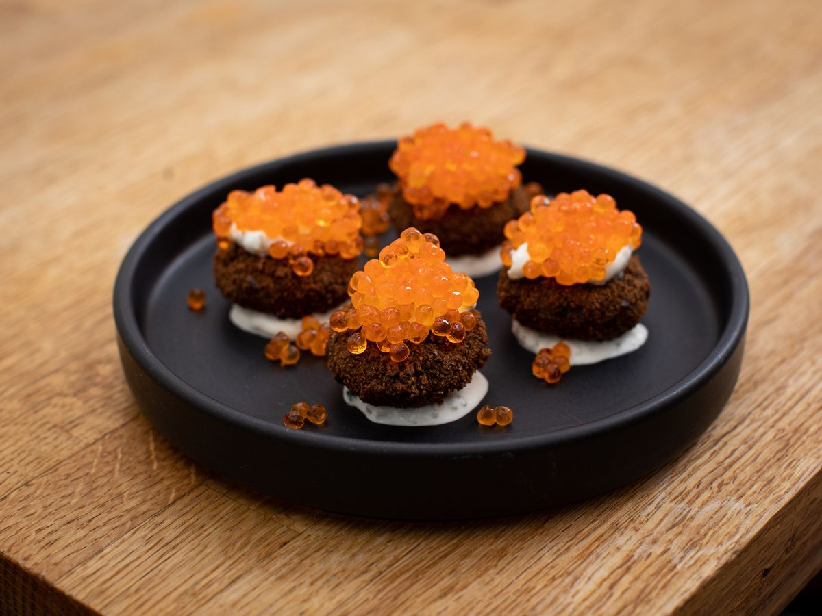 Four ornate fried croquettes, resting on a bed of white liquid and topped with orange roe
