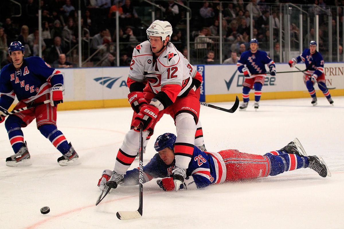 NEW YORK - NOVEMBER 11: Eric Staal #12 of the Carolina Hurricanes controls the puck from a diving Ruslan Fedotenko #26 of the New York Rangers at Madison Square Garden on November 11, 2011 in New York City.  (Photo by Chris Trotman/Getty Images)