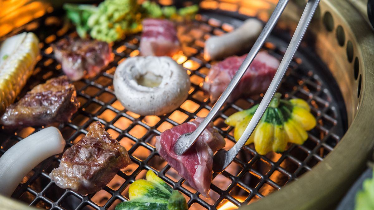 A variety of meats sear over a tabletop grill at Cote