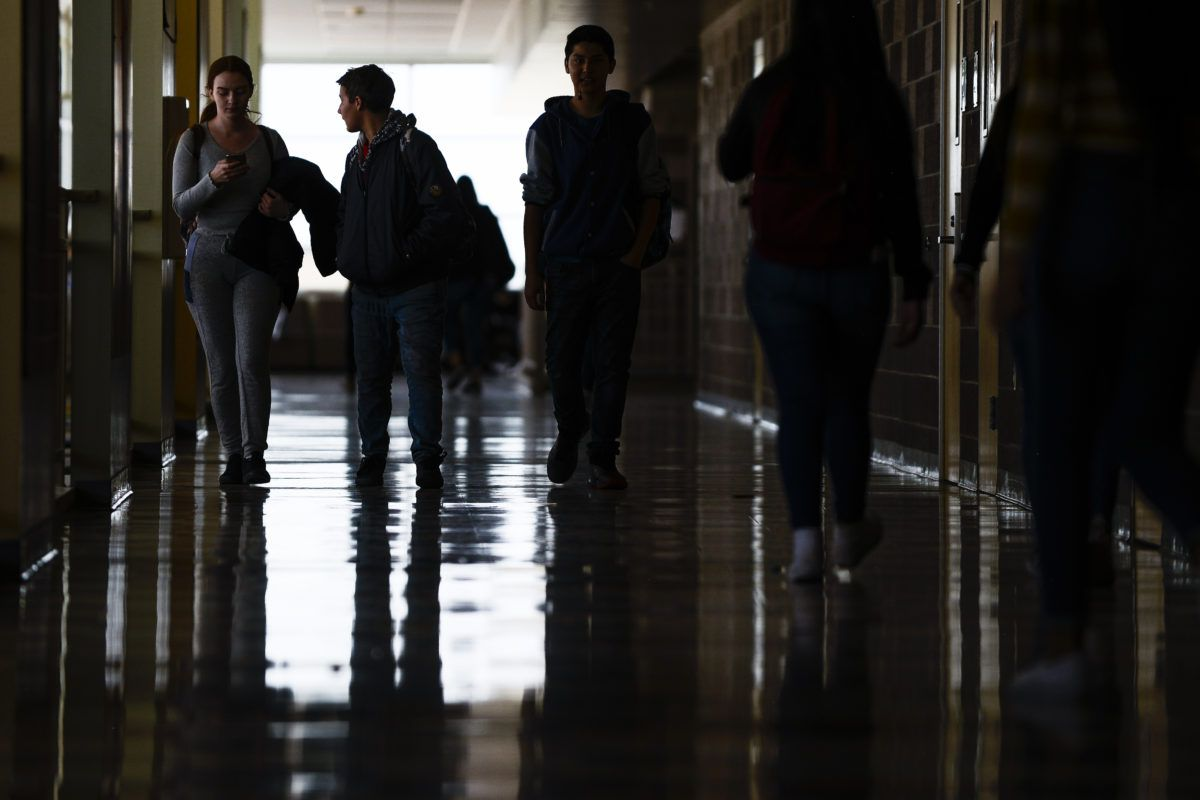 High school students walk through a wide and dark hallway at Adams City High School. There's a window behind them that illuminates the floors.