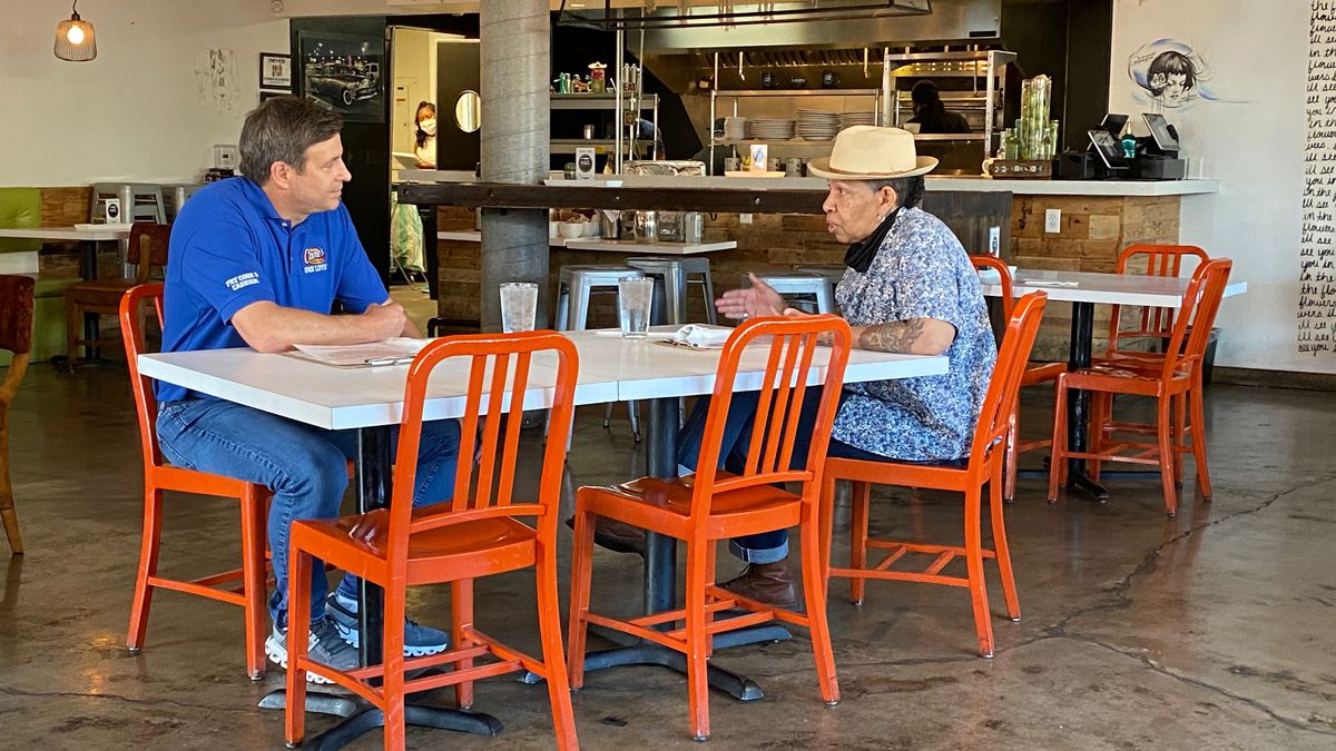 A man in a blue shirt and a woman in a blue shirt and hat sit at a table with orange chairs
