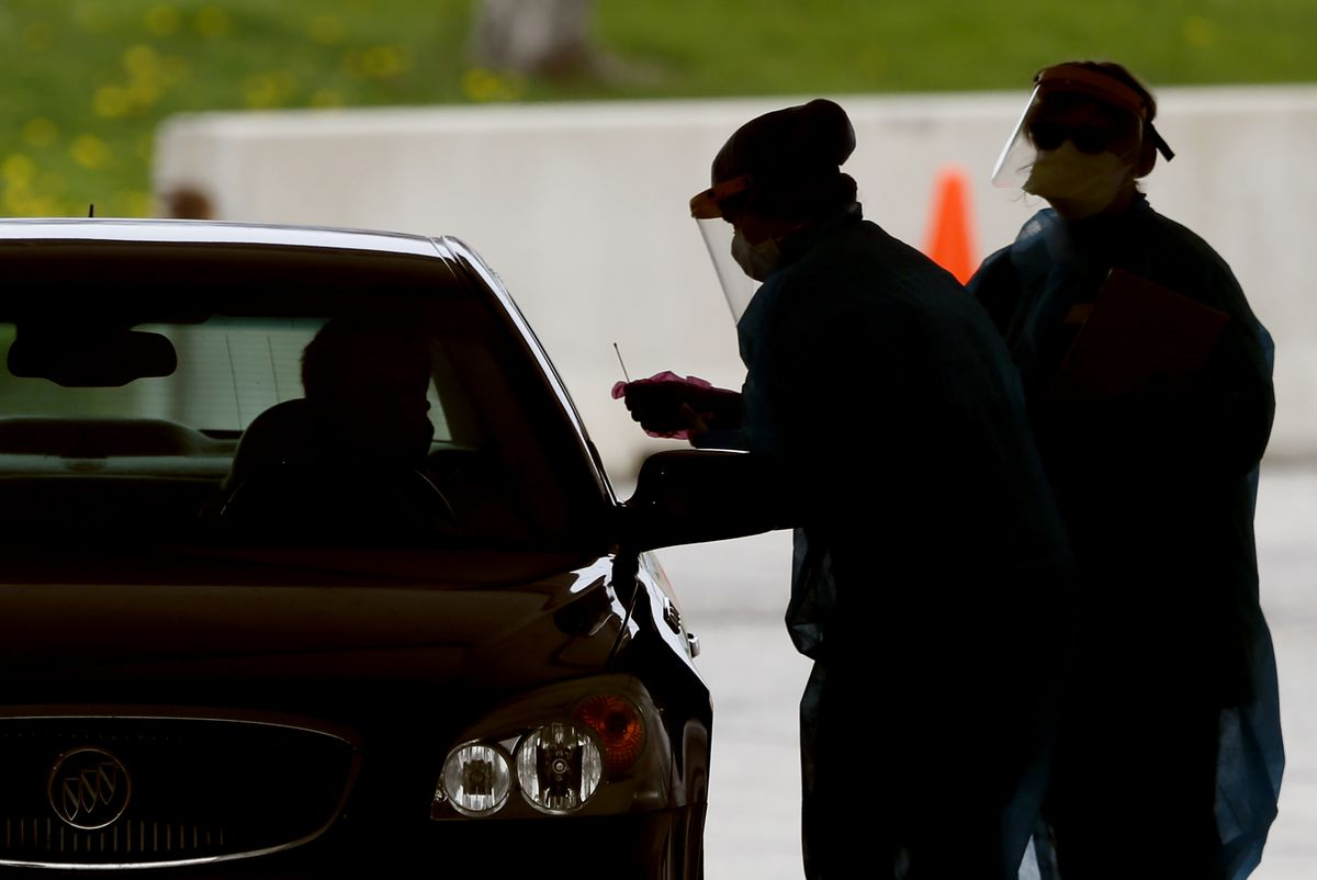 Two masked figures in shadow stand next to the driver's side window of a car.