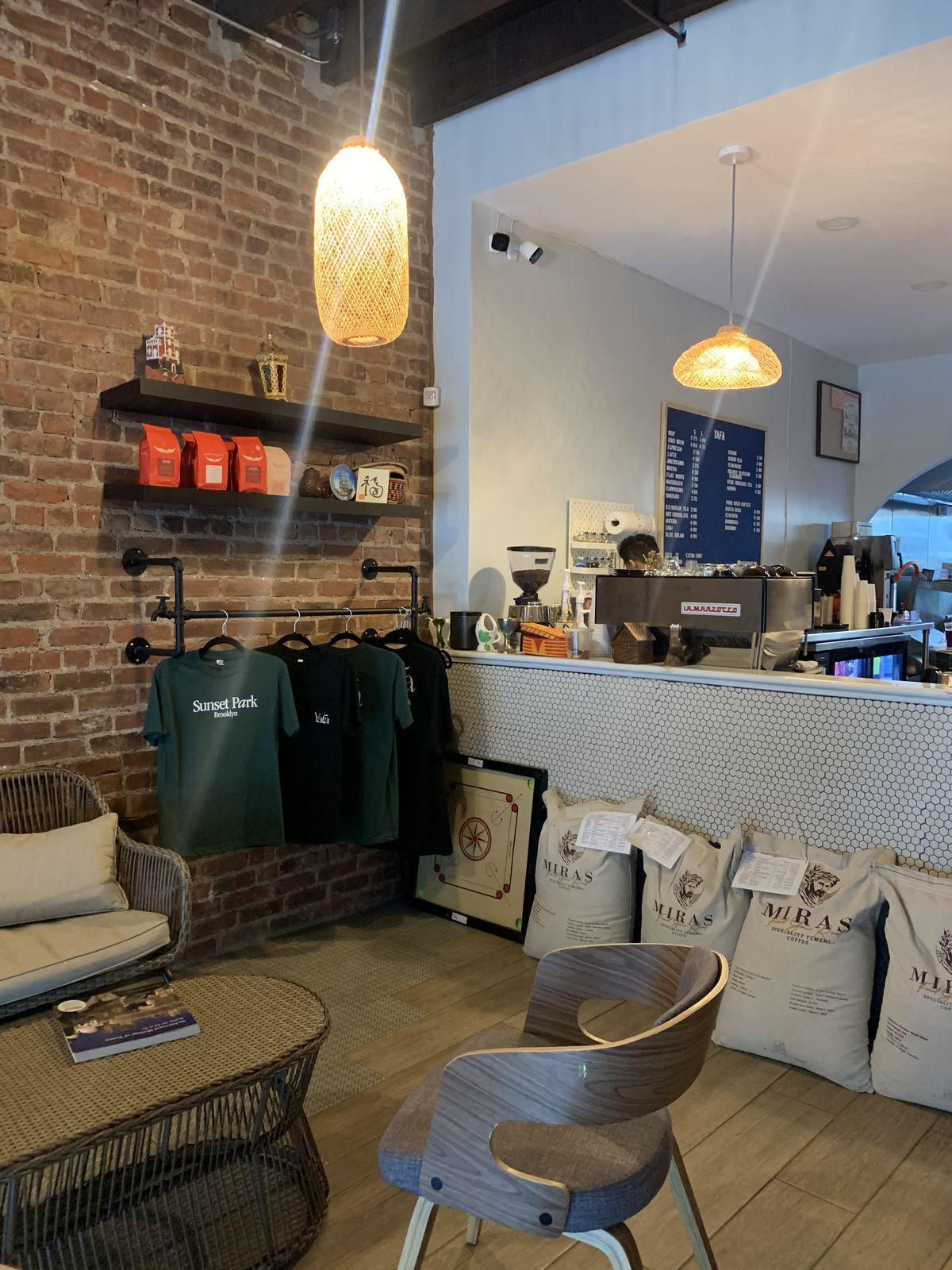 A cafe with a white counter and espresso machines, with green t-shirts hanging against the wall.